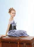 Little girl sitting on a suitcase. Beautiful little girl in a long Princess dress , sitting on an old road suitcase.On the pale blue background Royalty Free Stock Images