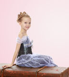 Little girl sitting on a suitcase. Beautiful little girl in a long Princess dress , sitting on an old road suitcase.Pale pink gradient background Stock Photography