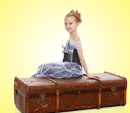 Little girl sitting on a suitcase. Beautiful little girl in a long Princess dress , sitting on an old road suitcase.On a yellow gradient background Stock Photos