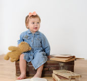 Little girl sitting on suitcase near book Royalty Free Stock Images