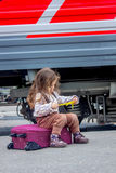 Little girl sitting at suitcase on railway station with the train on background. Little girl sitting at railway station with the train on background Royalty Free Stock Image