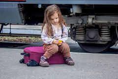 Little girl sitting at suitcase on railway station with the train on background. Little girl sitting at railway station with the train on background Stock Images