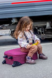 Little girl sitting at suitcase on railway station with the train on background. Little girl sitting at railway station with the train on background Stock Image