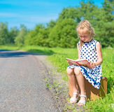 Little girl sitting on suitcase and reading book. Royalty Free Stock Image