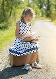 Little girl sitting on suitcase and reading book. Stock Images