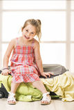 Little girl sitting on a suitcase, ready for travel Royalty Free Stock Photo
