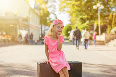 Little girl sitting on suitcase and thinking Royalty Free Stock Images