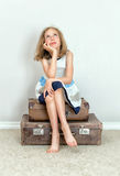 Little girl sitting on suitcases. Stock Photography
