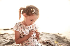 Little girl sitting on a sunlit beach at sunset, playing Stock Photos