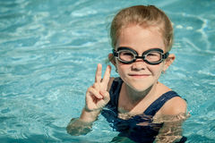 Little girl sitting in the swimming pool Stock Image