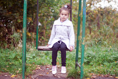 Little girl sitting on a swing Stock Image