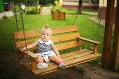 Little girl sitting on swing Stock Photo