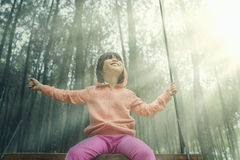 Little girl sitting on a swing outdoors Royalty Free Stock Image