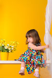 Little girl sitting on swings with flowers indoors Stock Image