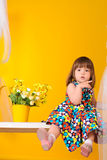 Little girl sitting on swings with flowers indoors Stock Images