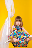 Little girl sitting on swings indoors Stock Photo