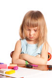 Little girl sitting at a table. With his arms folded and head lowered Stock Photos