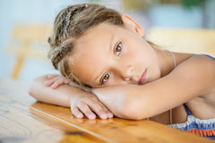 Little girl sitting at table Stock Photos