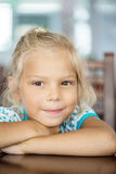 Little girl sitting at table Royalty Free Stock Images