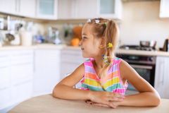 Little girl sitting at table Stock Photography