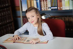 Little Girl Sitting At Table With Books Royalty Free Stock Photography