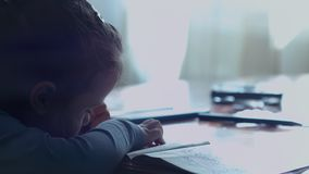 Little girl sitting at the table drawing in a coloring book early in the morning stock footage