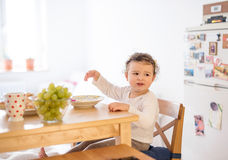 Little girl sitting at the table, eating breakfast Royalty Free Stock Images