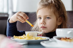 Little girl sitting at table and eating French fries Royalty Free Stock Images