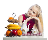 Little girl sitting at the table Stock Images