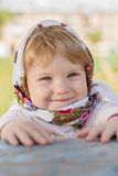 Little girl sitting at the table. A little girl in a headscarf sitting at the table Stock Photo