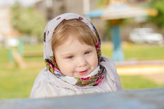 Little girl sitting at the table. A little girl in a headscarf sitting at the table Royalty Free Stock Photos