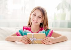 Little girl sitting at a table and holding gift box Stock Photo