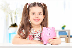 Little girl sitting at table and holding a piggybank indoors Stock Images