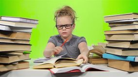 Little girl sitting at the table and nervously throws book. Green screen. Slow motion stock video