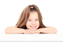 Little girl sitting on table and posing isolated on white backgr Royalty Free Stock Photo