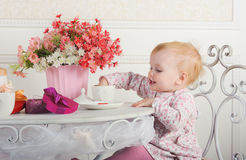 Little girl sitting at a table with tea and decorations, portrai Stock Photo