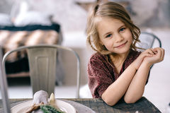 Little girl sitting at the table. Little girl sitting at a wooden table in the Marsala-colored dress Stock Images