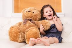 Little girl sitting with teddy bear on sofa. Royalty Free Stock Photo
