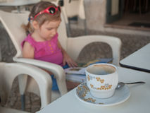 A little girl sitting on a terrace of a street cafe with a cup of hot drink and reading a travel guide Royalty Free Stock Photography