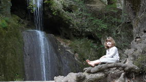 Little girl sitting to a waterfall stock video footage