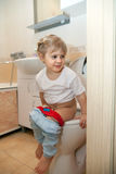 Little girl sitting on   toilet i Stock Photography