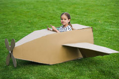 Little girl sitting in toy plane while playing on green lawn in park Stock Photos