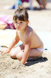 Little girl sitting at tropical beach. Royalty Free Stock Photo