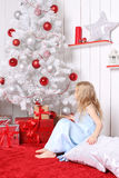 Little girl sitting under the Christmas tree and looking for presents. Royalty Free Stock Images