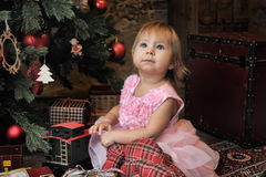 Little girl sitting under the Christmas tree Stock Images