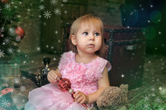 Little girl sitting under the Christmas tree Stock Photos