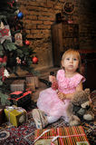Little girl sitting under the Christmas tree Royalty Free Stock Photos