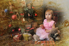 Little girl sitting under the Christmas tree Royalty Free Stock Images
