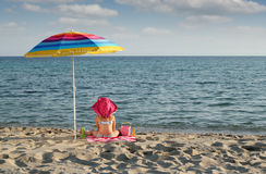 Little girl with sitting under sunshade on beach Royalty Free Stock Photos