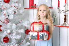 Little Girl Sitting Under The Christmas Tree. Stock Photos